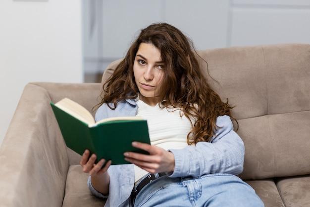 Красивая молодая женщина отдыхает дома, сидя на диване и читая интересную книгу