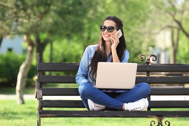 ノートパソコンと携帯電話で公園で休んでいる美しい若い女性