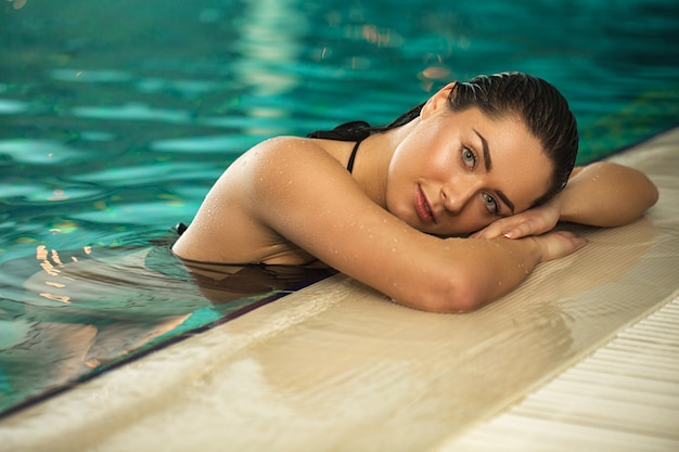 Beautiful young woman resting in the pool at spa center