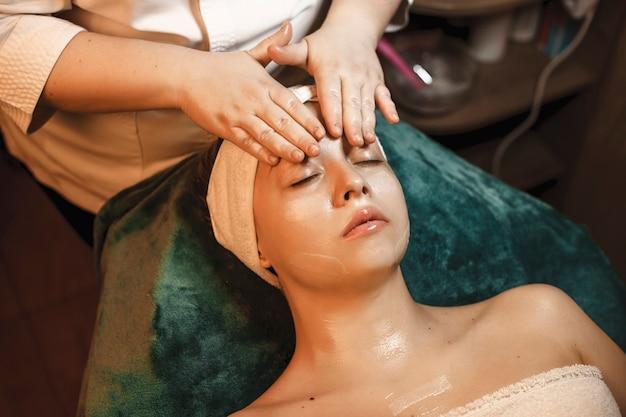 Красивая молодая женщина отдыхает во время массажа лица в оздоровительном спа-центре.