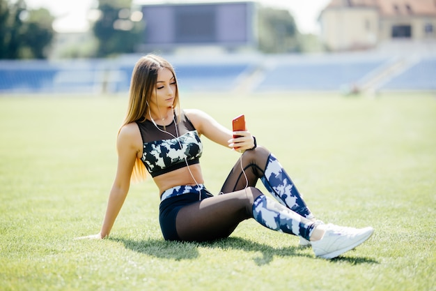 Beautiful young woman rests on the field listening to music