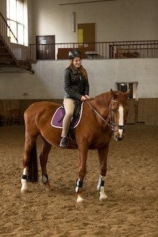 Beautiful young woman riding brown horse in indoor manege