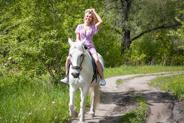 夏の暖かい日に森で無料の白い馬に乗って美しい若い女性。ファッションモデルの女の子と馬との屋外写真。ライフスタイル気分