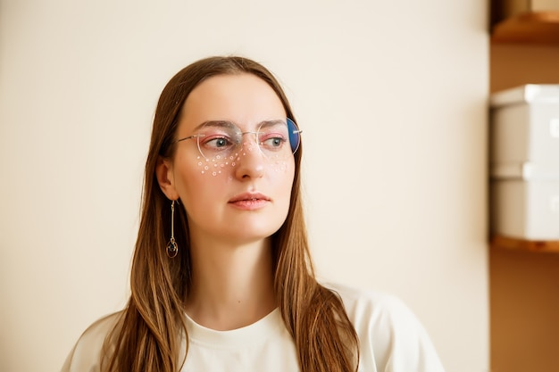 A beautiful young woman in round glasses with pink stars glitter around her eyes