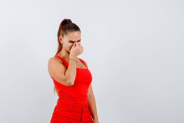 Bella giovane donna strofinando gli occhi e il naso in canottiera rossa, pantaloni e guardando sconvolto, vista frontale.
