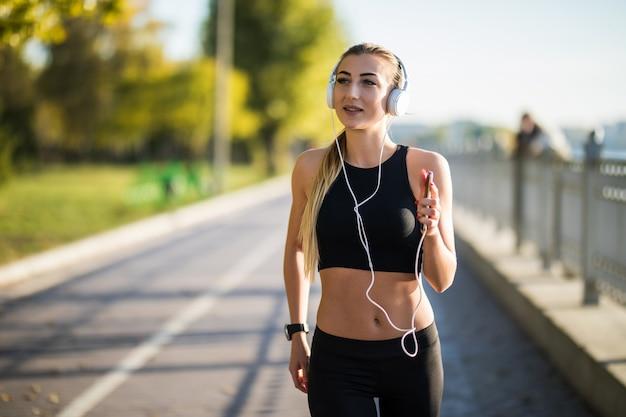 Bella giovane donna che corre nel parco verde nella soleggiata giornata estiva