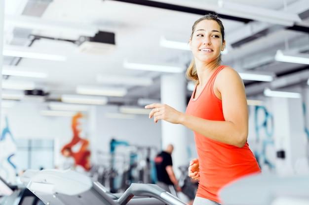 체육관에서 러닝머신 위에서 달리고 웃고 있는 아름다운 젊은 여성