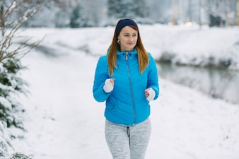 Beautiful young woman running on snowy landscape