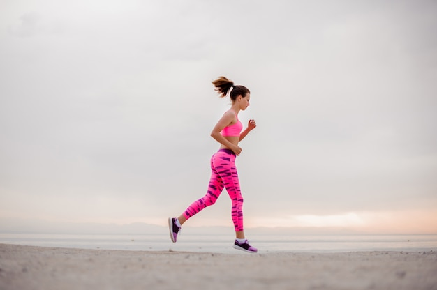 Beautiful and young woman running over the seaside in the morning