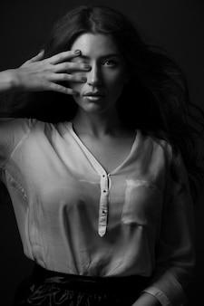 彼女の手が彼女の目を隠している美しい若い女性の白黒の肖像画。