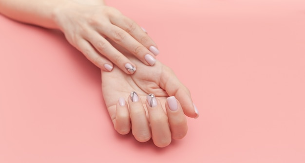 Beautiful young woman's hand with perfect manicure on pink
