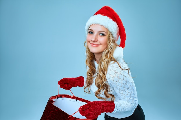 Beautiful young woman in santa claus clothes with a gift on blue