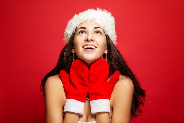 Beautiful young woman in santa claus hat and mittens smiling. christmas tale. postcard. copyspace. red .