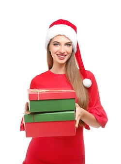 Beautiful young woman in santa hat holding giftboxes, on white background