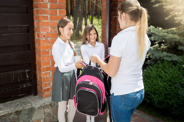 Beautiful young woman seeing off her daughters to school