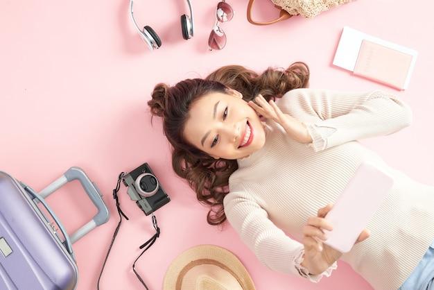 彼女の旅行の荷物を持つピンクの床で美しい若い女性の自撮り