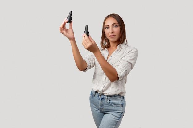 Красивая молодая женщина серьезно смотрит в камеру, держа бутылки лака для ногтей красоты портрет б ...