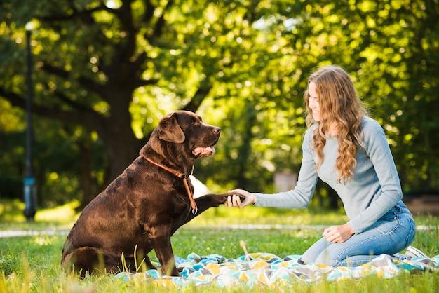 Beautiful young woman shaking dog's paw in garden