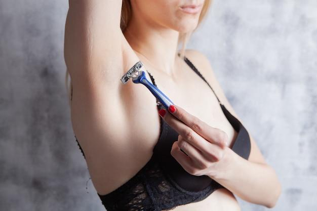 Beautiful young woman shaving armpits