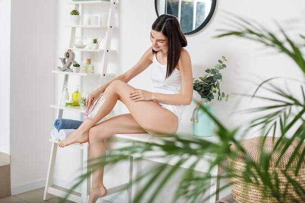 Красивая молодая женщина, бреющая ноги в ванной комнате