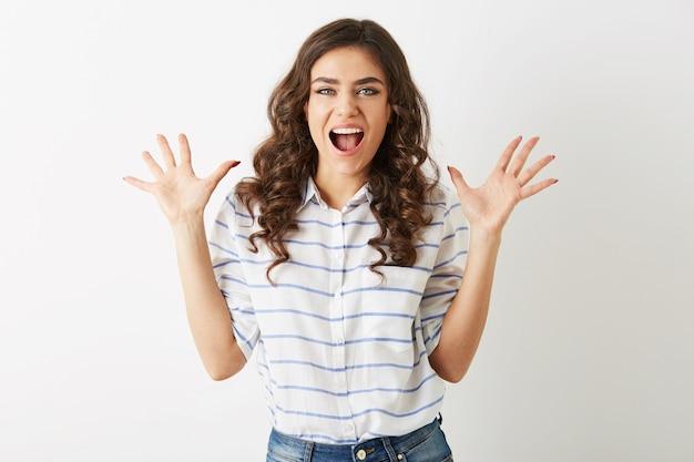 Красивая молодая женщина, потрясенная, подростковый хипстерский стиль, вышла, одетая в рубашку, изолированную на белом фоне, современная мода, руки вверх, открытый рот