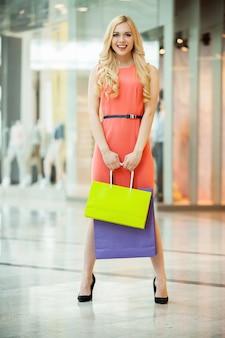 Красивые покупки молодой женщины. полная длина красивой молодой женщины, стоящей в торговом центре с хозяйственными сумками