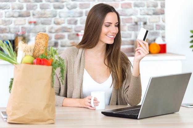 Красивая молодая женщина, покупки с ее карты онлайн на кухне.