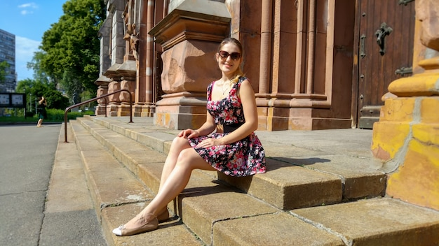Beautiful young woman in short dress sitting on old stone stairs on street of town