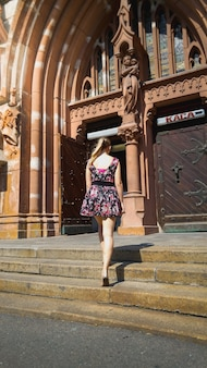 Beautiful young woman in short dress standing on old stone stairs at catholic cathedral at european town