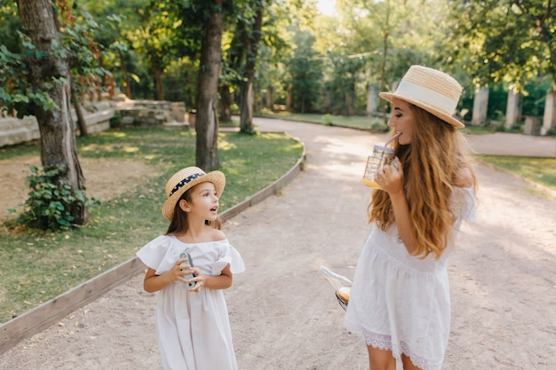Beautiful young woman in short lace dress drinking juice and talking with daughter on alley. pretty tanned girl in straw hat looking at mother enjoying cocktail in warm sunny day.