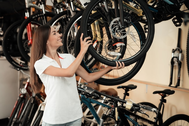 Beautiful young woman show row of modern bicycles