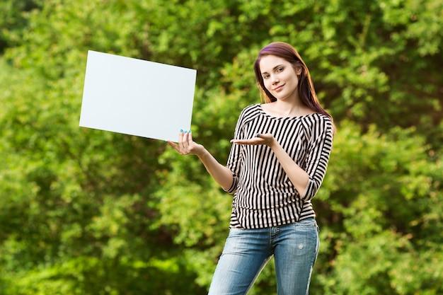 空白の白いバナーを示す美しい若い女性
