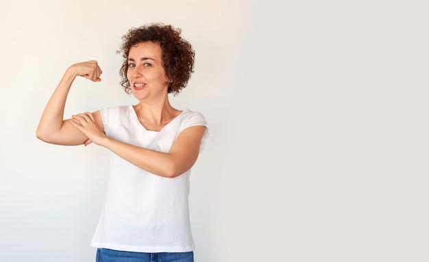強さと健康を表現する上腕二頭筋を示す美しい若い女性