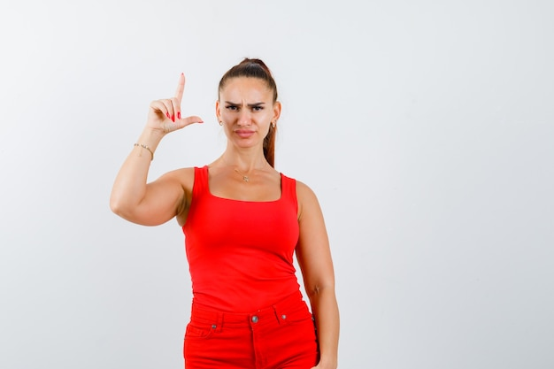 Beautiful young woman showing gun gesture in red tank top and looking serious. front view.