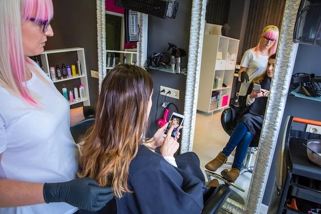 스마트폰으로 헤어스타일 사진을 미용사에게 보여주는 아름다운 젊은 여성