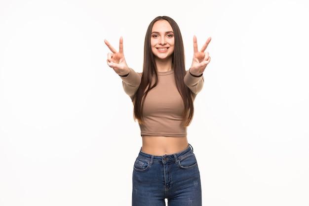 Bella giovane donna che mostra il segno di vittoria di pace isolato sulla parete bianca