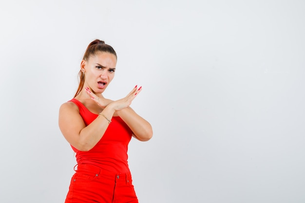 赤いタンクトップ、パンツ、毅然とした表情で拒否ジェスチャーを示す美しい若い女性。正面図。