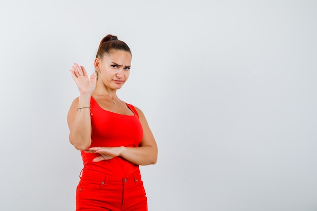 Beautiful young woman showing stop gesture in red tank top, pants and looking displeased , front view.
