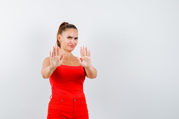 Beautiful young woman showing stop gesture in red tank top, pants and looking scared , front view.