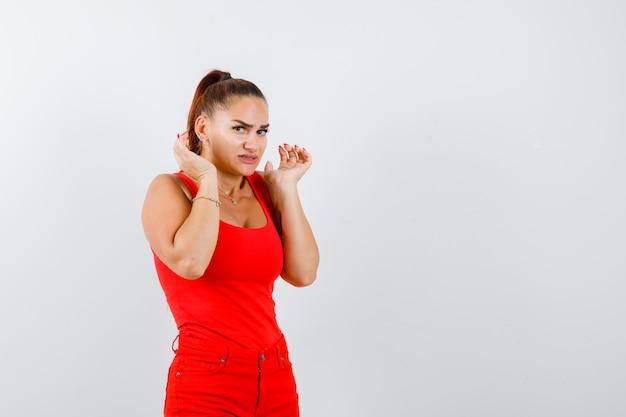 Красивая молодая женщина показывает жест капитуляции, пожимая плечами в красной майке, штанах и испуганно, вид спереди.