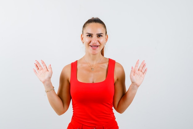 Bella giovane donna che mostra gesto di resa in canottiera rossa e che sembra allegra. vista frontale.