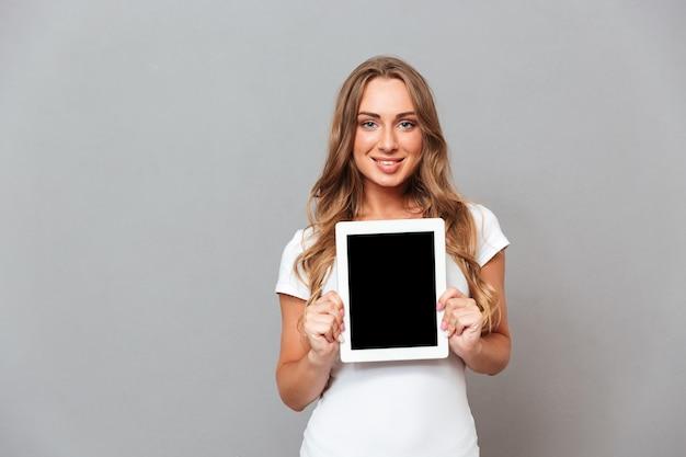 灰色の壁に分離された空白の画面でタブレットコンピューターを示す美しい若い女性