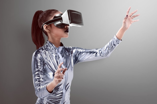 Beautiful young woman in silver latex costume and vr headset