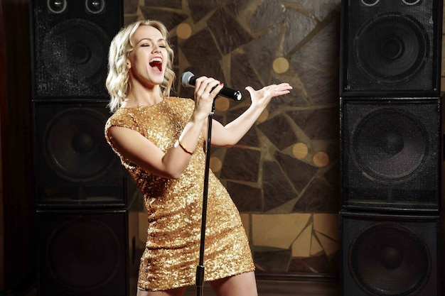 마이크와 노래하는 아름 다운 젊은 여자