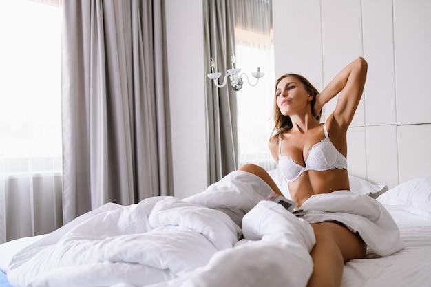 美しい若い女性は、高級ホテルの朝のベッド、白いシーツのあるアパートに座って、開いた窓のカーテン、ストレッチネックのレースのランジェリーを着て、素晴らしい一日を始めましょう