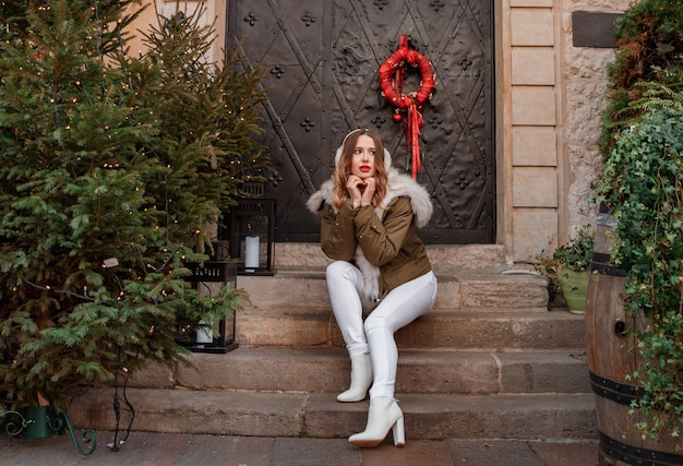 クリスマスツリーの近くの階段に座っている美しい若い女性
