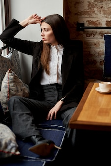 A beautiful young woman sits in a cafe behind a glass with a cup of coffee and looks thoughtfully out the window.