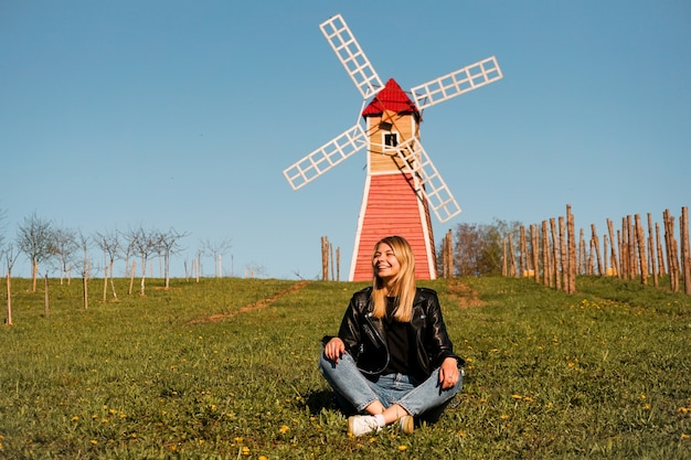 Beautiful young woman sits on the grass against the backdrop of the red mill.