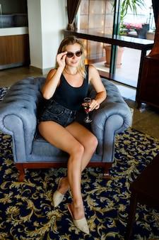美しい若い女性は、休暇中にシャンパングラスを片手にホテルのロビーの柔らかいアームチェアに座っています。彼女はサングラスと笑顔を着ています。休暇の概念