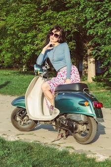 Красивая молодая женщина сидит на скутере. стильная девушка на мопеде.